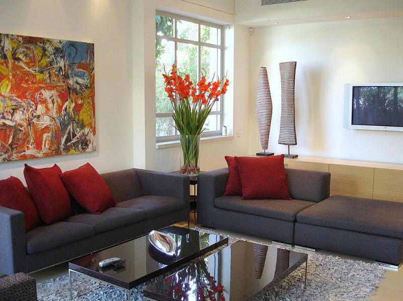 gray sofas in living room with red flowers and cushions