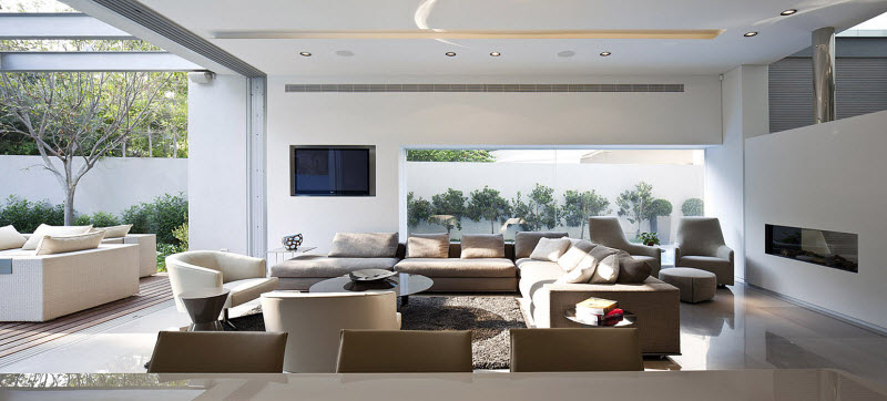 open living room with brown sofas and white chairs
